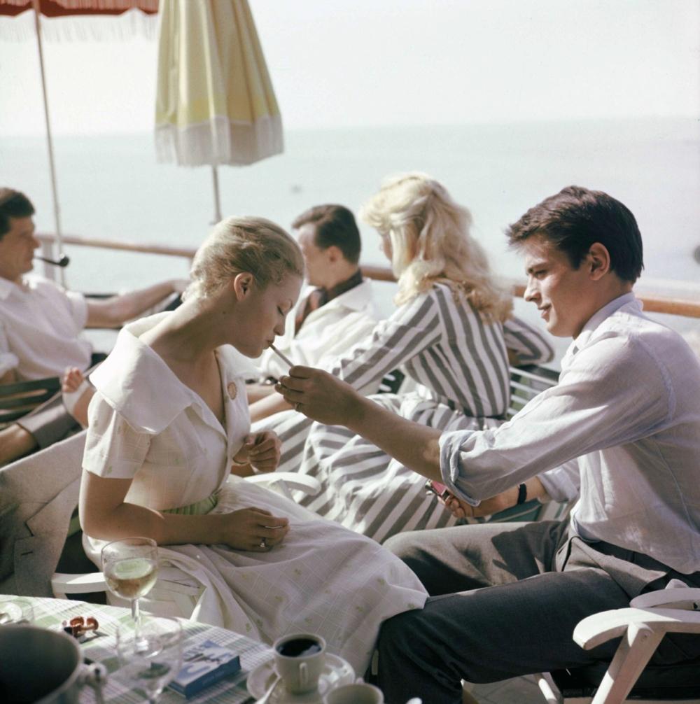 """Romy Schneider et Alain Delon déjeunent en terrasse. La belle autrichienne n'en était pas à son premier festival, elle était déjà venue en 1957 défendre """"Sissi Impératrice""""..."""